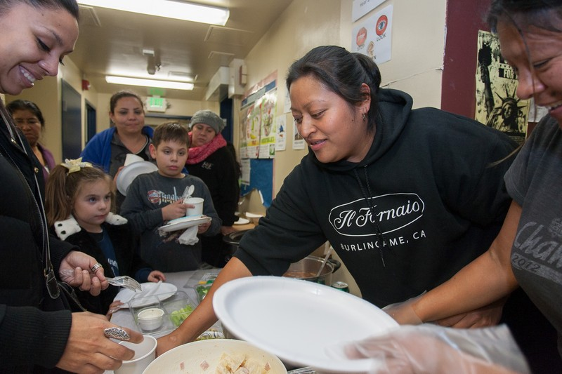"""Ana Hernandez serves food at a monthly dinner party hosted by Junipero Serra's PTA. She first got involved by working on the school's food bank, distributing food to hungry families. This school year, the PTA aims to raise around $7,000 to support field trips, buy computers, get gifts for the teachers and underwrite the fifth-grade graduation project. The PTA also sets aside part of that fund to support Junipero Serra families facing economic emergencies. Because almost all the school's families live in poverty, their financial contributions tend to be modest. """"They can help with one dollar, two dollars,"""" Hernandez said. """"Even when they have no money, people help in different ways."""" Photo: Luke Thomas / San Francisco Public Press"""
