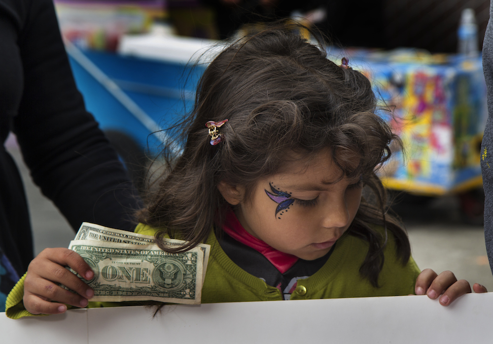 A child buys tickets at the Halloween-Día de los Muertos fundraiser for Junipero Serra Elementary in Bernal Heights. The event netted $3,000 for the PTA. Photo by Tearsa Joy Hammock / San Francisco Public Press