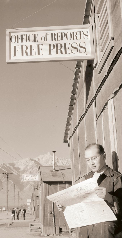 editor_roy_takeno_reading_a_copy_of_the_manzanar_free_press.png