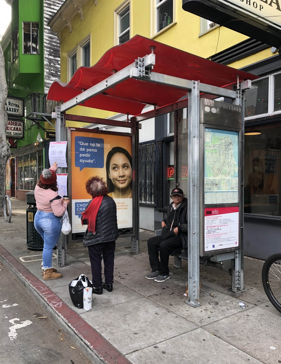 A woman shows signs about cancelled bus routes to another woman who had been sitting at a bus stop at 24th and Folsom streets waiting for the 48 Quintara/24th St. bus on April 8.
