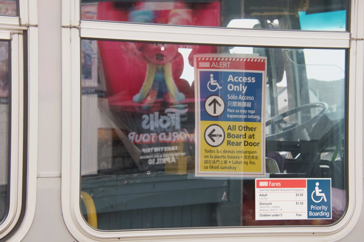 A sign in the window of a 14 Mission bus, one of the few Muni routes still running on April 8, asks riders to board through the rear door to keep social distance from the driver.