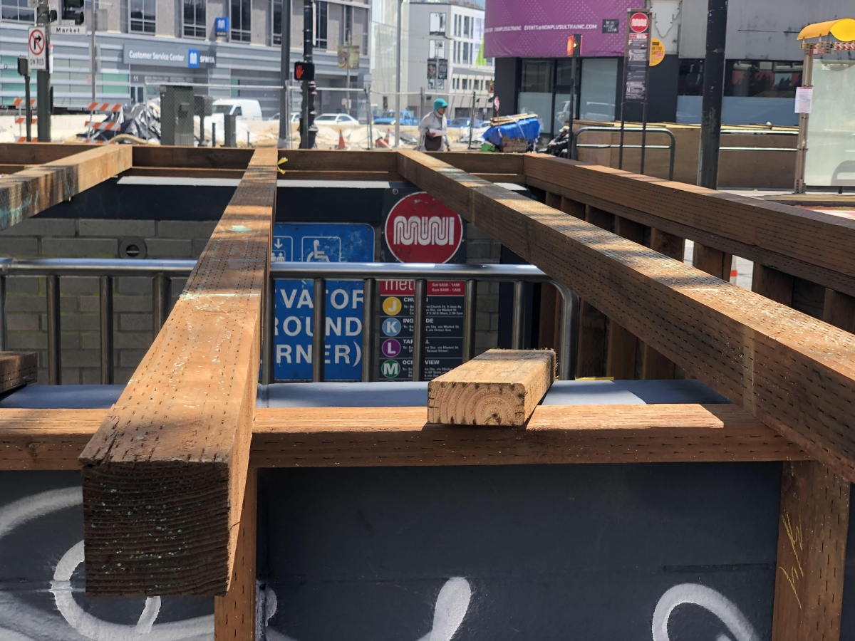Workers started boarding up an entrance to the Van Ness Muni stop on April 10. Muni headquarters is within view across Market Street. In response to the pandemic, Muni stopped running all underground trains and replaced them with buses.