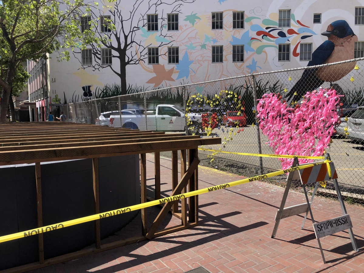 "An entrance to the Van Ness Muni stop is being boarded up on April 10 following Muni's decision to stop running underground trains and replace them with buses. Two hearts made of locks and ribbons on a fence are a regularly updated renegade art installation in front of the 6,000-square-foot ""Bird Song #3,"" the first mural designed by artist Joshua Coffyand painted by 30 volunteers in 2015."