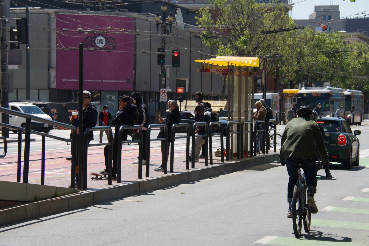 People wait at a stop on Market Street and Van Ness Avenue on April 10. A bus replacing the regular N Judah line and another bus going in the same direction are at another stop across the intersection.