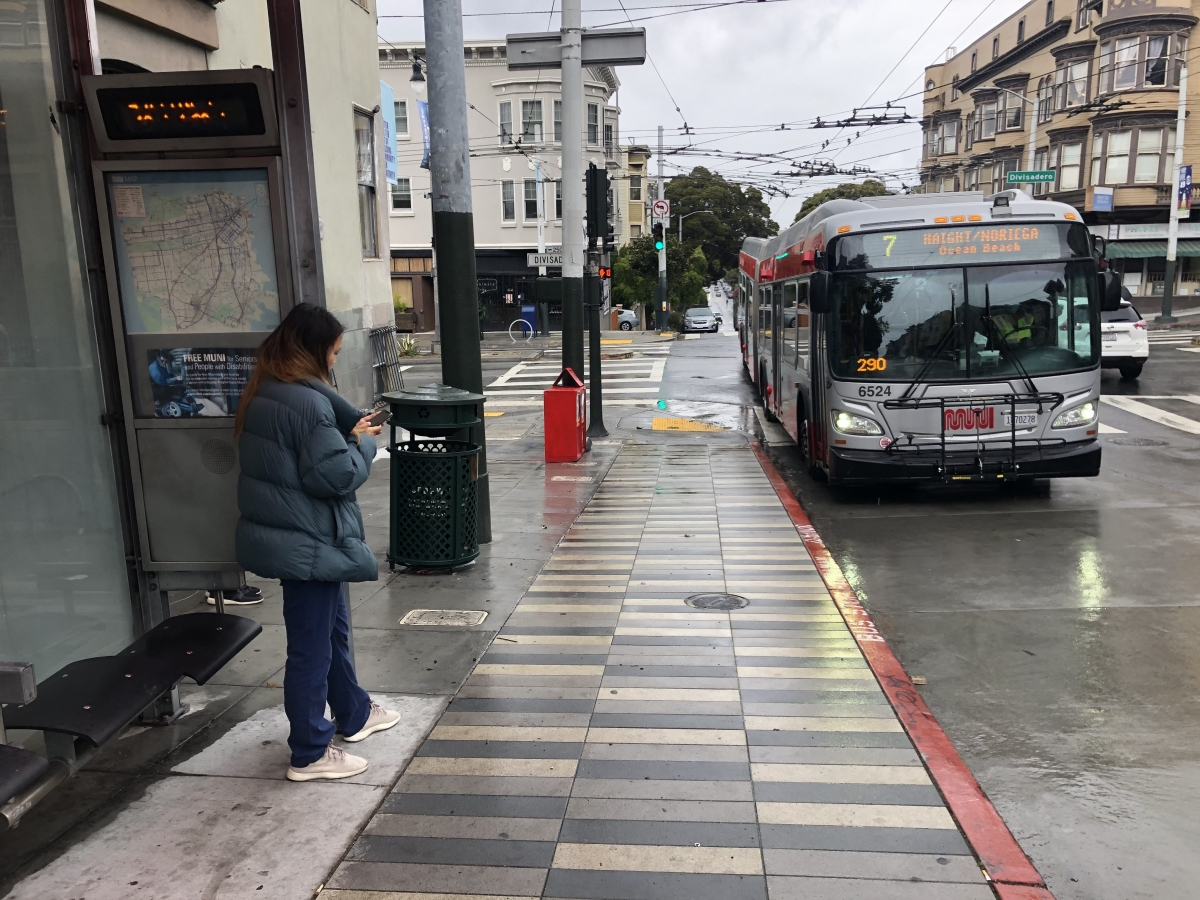 A woman waits on a rainy day for the 7 Haight/Noriega on Haight Street at Divisadero Street on April 6. It was the last day the 7 was running. It was among a smaller group of buses that stopped service on April 7 before wider Muni cuts took effect on April 8.