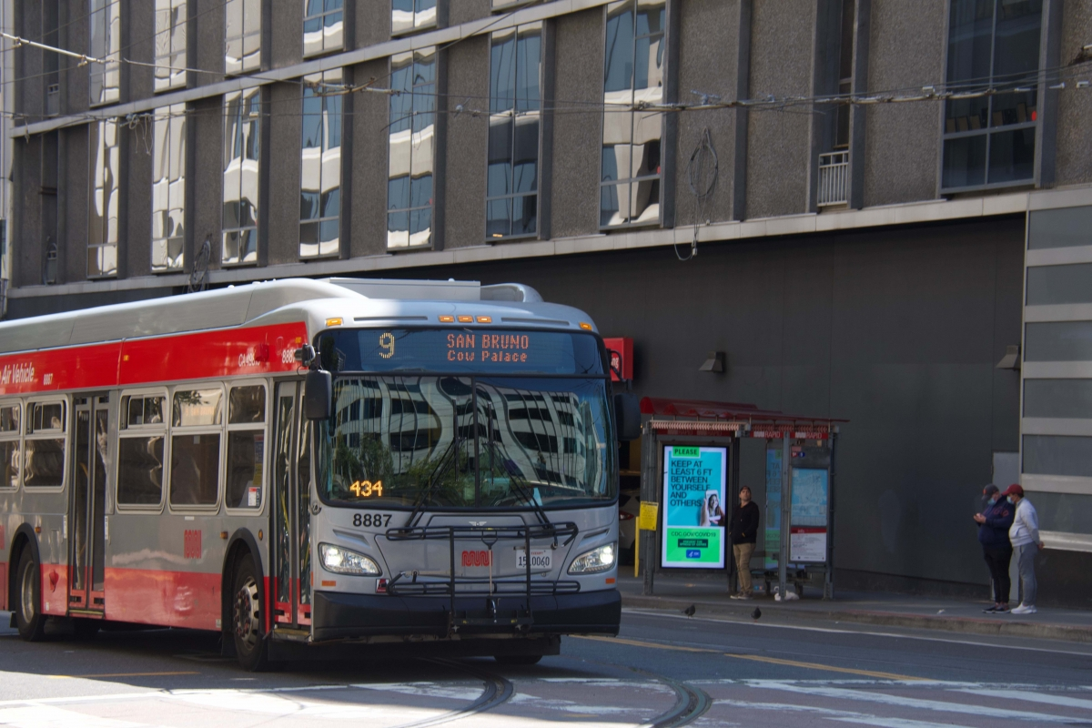 A 9 San Bruno bus is about to turn on to Market Street on April 10. Across the street, people wait at a bus stop, which displays several rotating digital CDC coronavirus public service announcements.