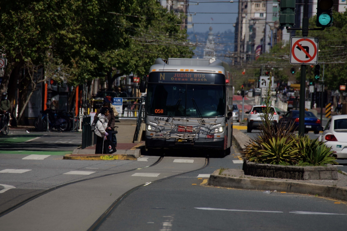People wait at a stop on Market Street as an N Judah bus approaches on April 10.