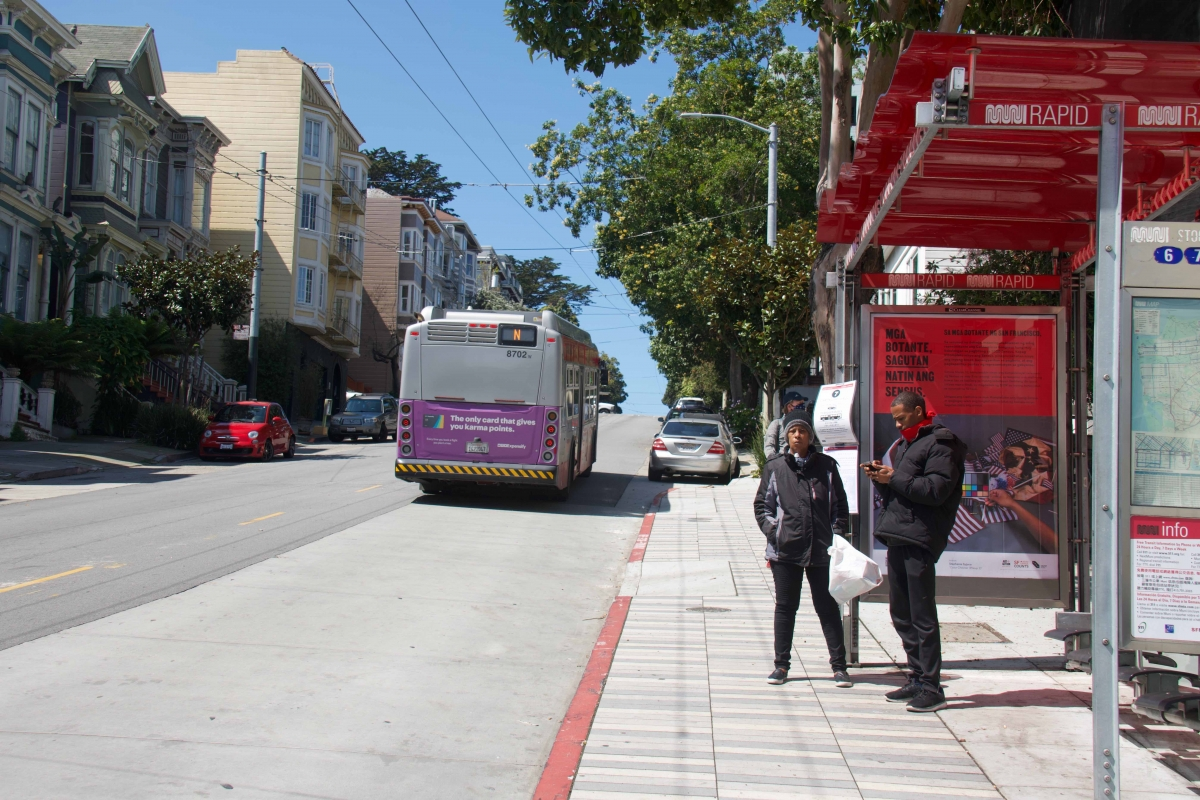 Two people wait for another bus after not boarding an N Judah bus on Haight Street at Divisadero Street on April 7. Service for the 7 Haight/Noriega, which normally stopped there, was cut on April 7, and for the 6 Haight/Parnassus on April 8.