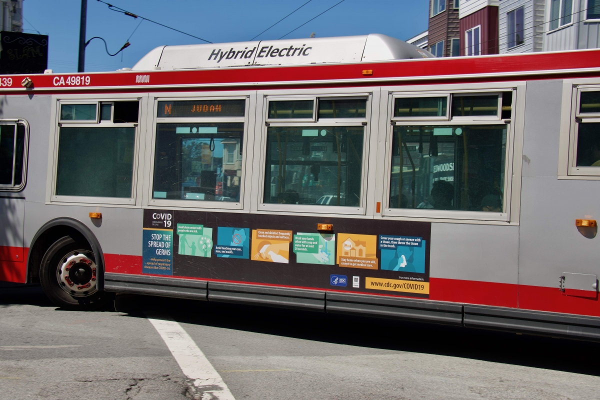 An N Judah bus with a CDC coronavirus public service announcement on the side turns off Haight Street on April 7. The 6 and 7 buses, which typically ran on Haight Street, were cut because of the coronavirus pandemic.