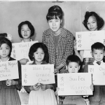 Six Chinese children who had recently arrived in New York City in 1964 with their teacher. The placards show their Chinese names, in ideographs and in transliteration, and the names to be entered in official school records. Library of Congress