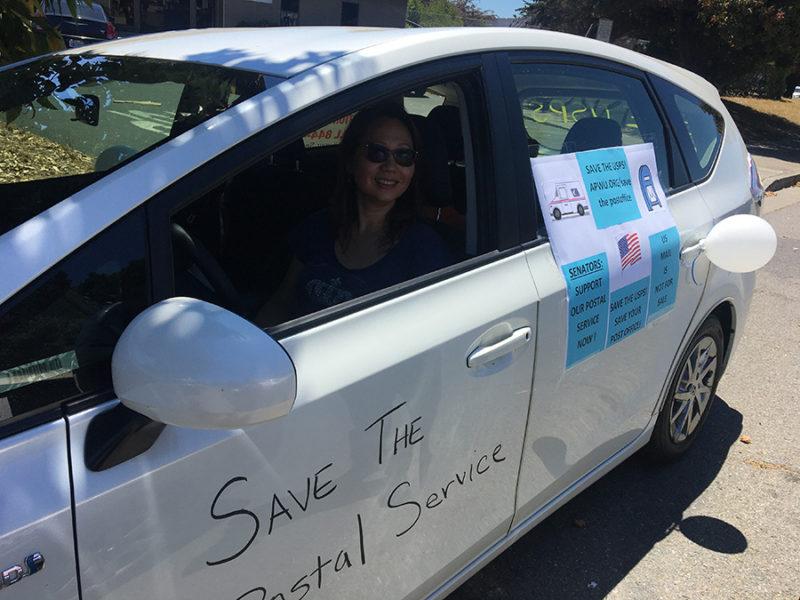 Cindy Datangel prepares to depart with the American Postal Workers Union car caravan in San Francisco. Laura Wenus / Public Press
