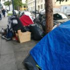 A homeless person sits under a blanket next to a cluster of tents in the Tenderloin May 13. Noah Arroyo / San Francisco Public Press