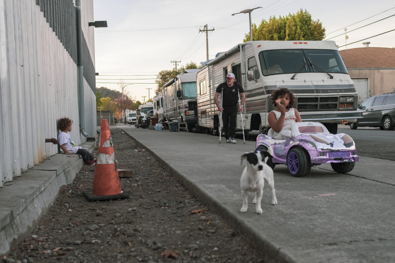 Un Domingo por la tarde, los niños juegan en el distrito de Gilman en West Berkeley. Su familia es parte de una comunidad de residentes de vehículos llamada Friends on Wheels, cuyos miembros se han estacionado y vivido juntos durante dos años. La comunidad está compuesta por familias, estudiantes, trabajadores de la economía gig y servicios, personas discapacitadas y de edad avanzada que viven en todo tipo de formas y tamaños de vehículos.