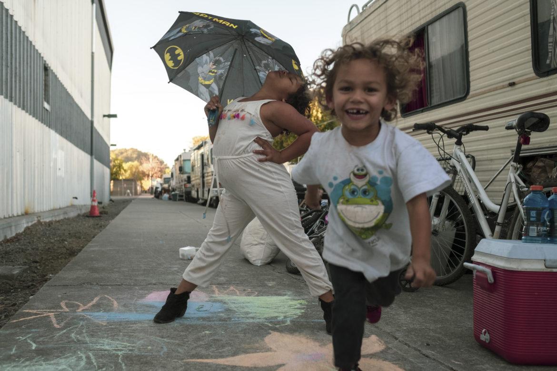 Los niños juegan en la calle Octava en West Berkeley mientras sus padres hacen mandados. Los vecinos que viven en vehículos recreativos o la abuela cuidan a los niños cuando los padres no están en casa. Los niños llenan el bloque con risas y juguetes mientras corren arriba y abajo de la línea de vehículos, mirando dentro de las puertas de los vecinos para saludar.