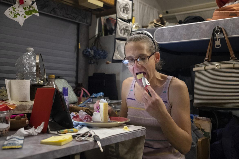Chloe Verron corta un trozo de queso y se lo come con su navaja en un vehículo de una amiga donde vive temporalmente. Verron vivía en un vehículo recreativo de 22 pies antes de que la policía de estacionamiento lo remolcara por tener el registro vencido. Las tarifas sumaron más de $ 3,000. Después de que el vehículo no fue reclamado por 30 días, se vendió en una subasta. Incapaz de comprar su casa, Verron ha estado navegando de sofá a sofá con miembros de la comunidad hasta que pueda ahorrar lo suficiente para comprar otro vehículo. Pero ahorrar dinero es un desafío, ya que no puede trabajar mientras se somete a un tratamiento hormonal. Antes de que Verron se quedara sin vivienda, alquiló una casa en el condado de Lake, cerca del Bosque Nacional de Mendocino, después de dejar un estresante trabajo de programación de computadoras con la firma de diseño Curran & Connors en Nueva York.