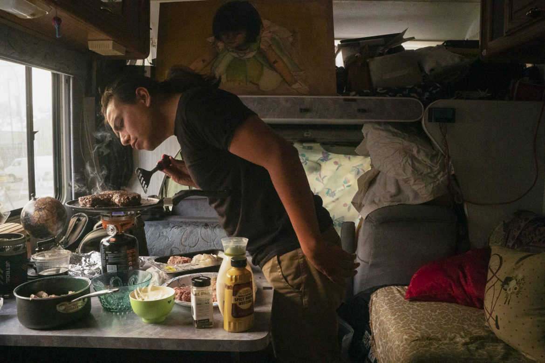 Christian Torres cocina hamburguesas en una estufa de campamento. Torres vive dentro de una camioneta de carga blanca Ford E150. Es fotógrafo de la ciudad de Sanger, cerca de Fresno. Trajo su camioneta al Área de la Bahía, buscando oportunidades creativas. Su rutina diaria: preparar el desayuno, ir al gimnasio, ducharse, viajar por la ciudad para comer y quedarse en cafeterías o bibliotecas para cargar baterías y aparatos electrónicos durante el día.