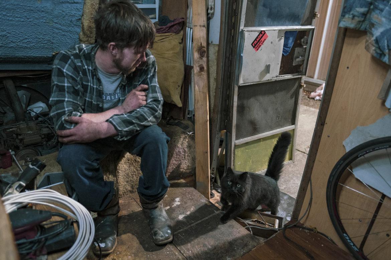 """Ryan Maddry se sienta en su vehículo recreativo esperando que su gato, llamado Dog, entre antes de acostarse a fines de Febrero. Después de vivir en una tienda de campaña durante meses en el campamento de la comunidad Here / There (La Comunidad Ni Aquí / Ni Alla), compró un vehículo recreativo como un paso hacia una vivienda estable. Llamó a su vehículo """"Ole Gal."""""""