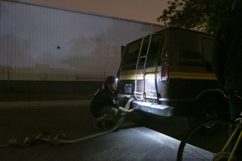 "Chris Castle ties a tow strap to the bumper of Amber Whitson's Dodge van on a Sunday night to help his friend Ryan Maddry, whose vehicle was red-tagged with a 72-hour notice, giving him a warning to move or be towed. But the ""Ole Gal"" is in disrepair and barely makes it around the corner. As a last resort, vehicle residents band together and use human force, pushing their vehicles by hand or pulling them with ropes. It is challenging to find new parking places and get resituated every three days."