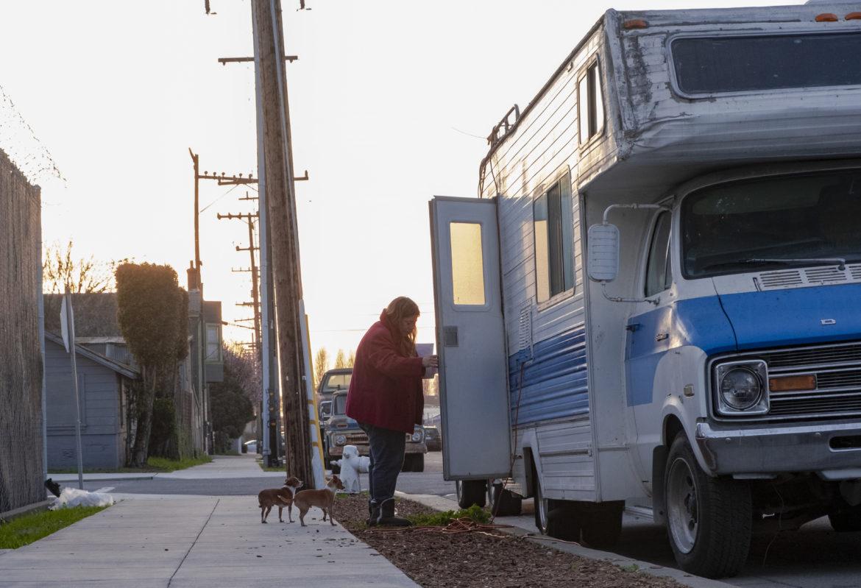 """Janet Enos regresa de la gasolineria con sus Chihuahuas, Scrappy y Pinky. Después de la muerte de la madre de Enos, ella perdió su vivienda y compró un vehiculo recreativo. Era su primera vez viviendo sola y alejándose de la casa familiar. Enos disfruta de las artes, manualidades y cocina. """"Me encanta alimentar a otras personas,"""" dijo. Con frecuencia prepara comida para compartir con los vecinos de al lado."""