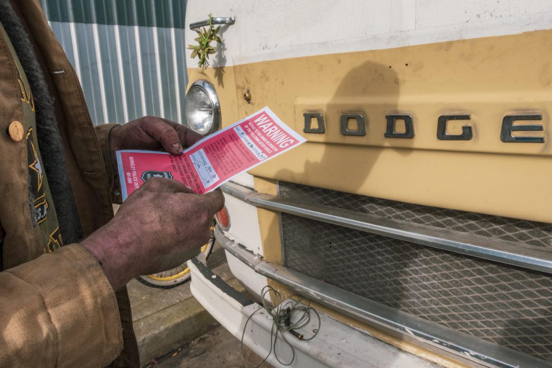 Ryan Maddry retira una etiqueta de advertencia de 72 horas del parabrisas de su vehiculo recreativo estacionado en las calles Octava y Harrison. Los avisos le dicen a los residentes del vehículo que se muevan cada tres días o corren el riesgo de ser remolcados.