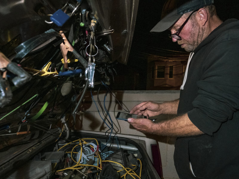 """Nelson rearranges the back of his car and recharges his phone. He sleeps on four stacked blankets in the back seat. Sometimes he folds down the seat to stretch his legs into the trunk. He has attached a solar panel to the roof to power essential electronics. """"The key to the solar deal is storage,"""" Nelson said. """"I have two batteries separate from the car, so I can run a television, a DVD player and charge up my phone. Now the next question is: How long can I run it for? I would be good for an hour or two. Anything crazy and heavy like a microwave or refrigerator is going to eat you up really quick."""" But bad wiring inside his trunk has proven hazardous. One afternoon while Nelson was charging his devices, an electrical short melted the plastic of the cigarette lighter plug and filled his car with smoke. """"I'm lucky I didn't kill myself,"""" he said."""