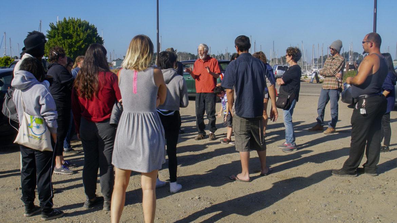 En el Día de los Caídos del 2018 (Memorial Day), el abogado de derechos civiles Osha Neuman explica a los residentes de vehículos en el pequeño puerto de Berkeley que sus esfuerzos para negociar un lugar sancionado para estacionarse allí han fallado, y tienen que mudarse o arriesgarse a ser remolcados. El personal de Waterfront publicó avisos de construcción en el lote del prado, lo que obligó a docenas de habitantes de vehículos a trasladarse a otras partes de la ciudad.