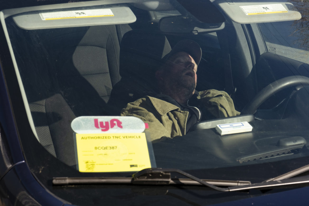 On a Saturday morning, Nelson sleeps inside his rented Lyft vehicle after an evening shift in the city. In late December, he began working for the ride-hailing company, helping him pay bills and buy food. The driving gig also helped him access resources and amenities around the city: restrooms, showers, laundry and electricity.