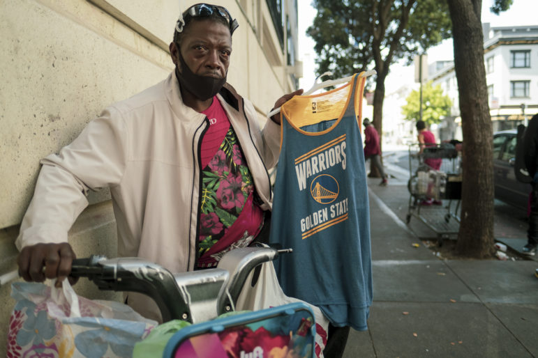 Damon, 47, walks his bicycle down a busy sidewalk in the Tenderloin neighborhood in late June, selling Warrior jerseys for $7. He packs his merchandise on his found Lyft bike and rides it for transportation, avoiding public transit and the coronavirus, he says.