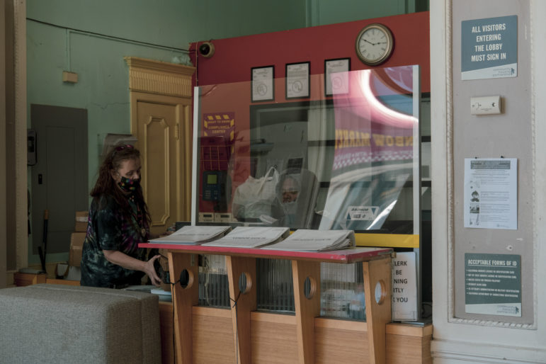 Kristi Banks picks up her mail from the reception desk of Hotel Essex. To prevent the spread of the coronavirus, the hotel installed plexiglass walls and posted safety guidelines. Residents must wear masks when entering the building. The hotel has about 100 rooms on seven floors.