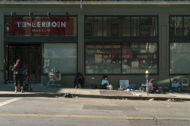 People congregate on the sidewalk to chat and sell found goods outside the Tenderloin Museum on Leavenworth and Eddy streets in late June.