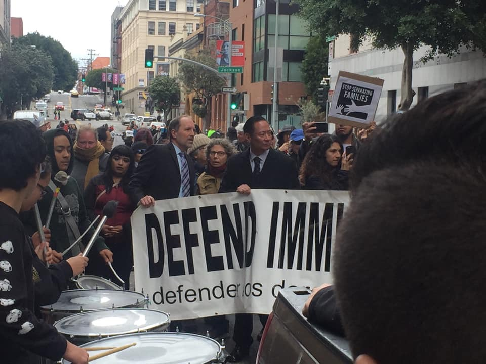 Francisco Ugarte, managing attorney of the San Francisco Public Defender's immigration defense unit, holds a banner with the late Public Defender Jeff Adachi at a community rally for immigrants' rights in 2018.