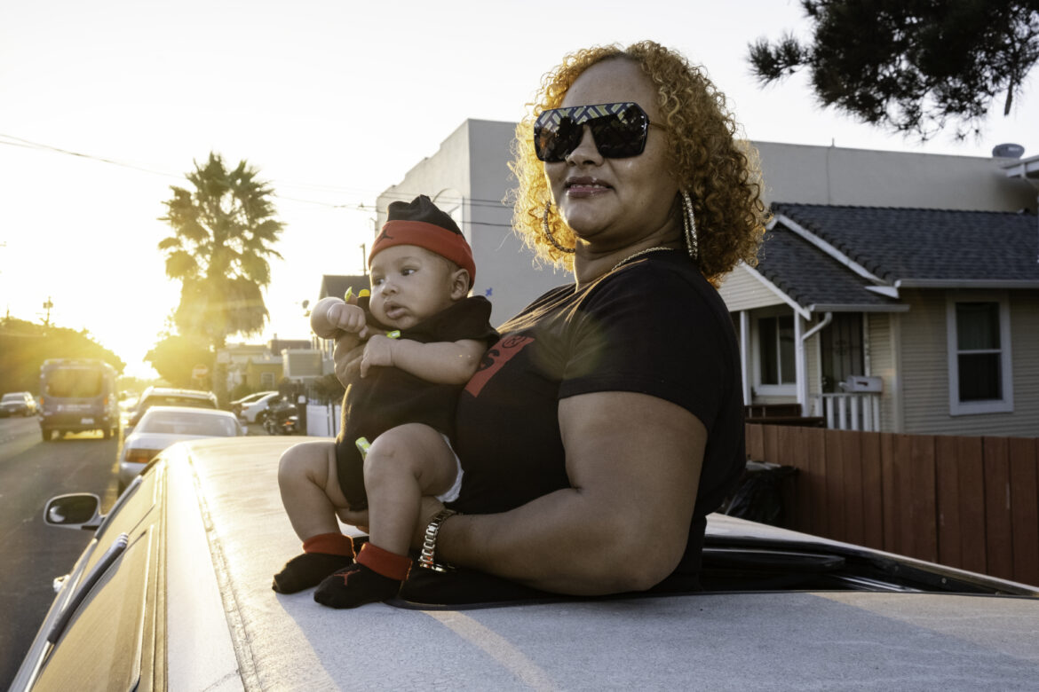 Tantay Tolbert holds her son Supreme Lloyd-Vaughn and poses for a portrait through a limousine sunroof in Richmond. Tolbert has a side business with her partner selling used vehicles, which she acquires from auto auctions. The couple fixes mechanical issues and sells the vehicles for a profit. In August, they acquired their first limousine with the intention of expanding their business into car rentals. But the coronavirus pandemic has slowed that side of the business, so the couple takes it out on Sundays for family party drives.