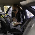 "Tolbert unbuckles Supreme's car seat as she prepares to go grocery shopping in San Francisco. She places him in a baby carrier on her chest for a more comfortable shopping experience. On this trip, Tolbert was loading up on food and household supplies for the month, so she can limit her trips during the pandemic. She enjoys being a stay-at-home mom and watching her son grow. ""I never expected to be a mother,"" Tolbert said. ""But here he is, right Papa?"" she said to Supreme."