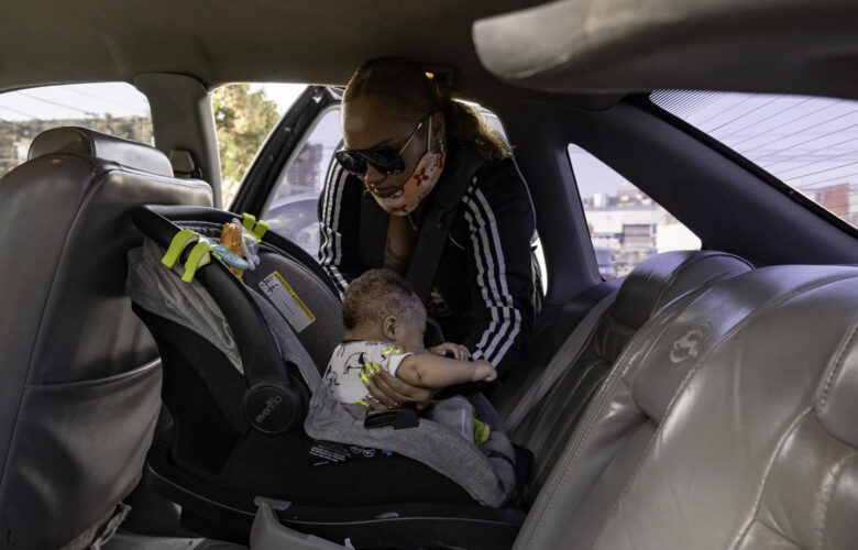 """Tolbert unbuckles Supreme's car seat as she prepares to go grocery shopping in San Francisco. She places him in a baby carrier on her chest for a more comfortable shopping experience. On this trip, Tolbert was loading up on food and household supplies for the month, so she can limit her trips during the pandemic. She enjoys being a stay-at-home mom and watching her son grow. """"I never expected to be a mother,"""" Tolbert said. """"But here he is, right Papa?"""" she said to Supreme."""