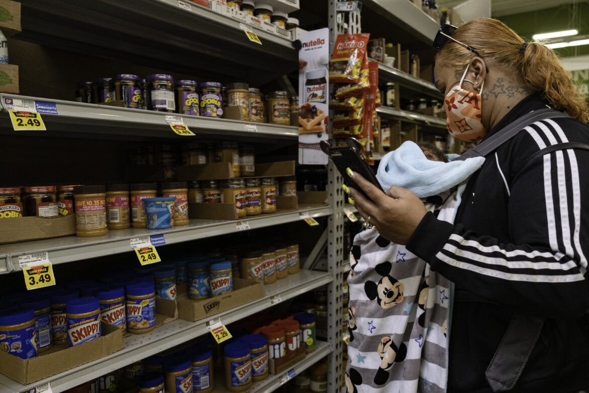 In the baking aisle, Tolbert scans a shelf of peanut butter jars looking for brands that she is eligible to purchase with her WIC benefits, which she can only use to buy specific food products from designated stores, preventing her from accessing healthier choices. She spends 20 minutes looking for items from the list on her phone, but only finds two in stock.