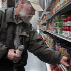 File photo: San Francisco Food Bank volunteer Jim Caddick stocks shelves with soup in 2012.
