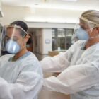 Ensign Kaitlyn Leibing, right, a staff nurse assigned to one of Naval Medical Center San Diego's internal medicine wards, helps Hospitalman Angela Mello don personal protective equipment before entering a COVID-19-positive, non-critical patient's room on Aug. 4, 2020.