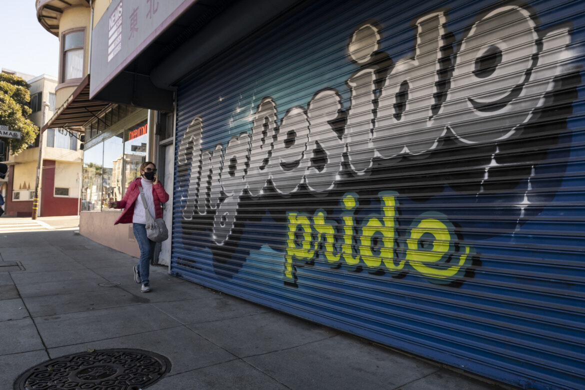 "A woman chats on her phone, wearing a mask,while walking down Ocean Avenue in early January.She strolls pass a mural highlighting, ""Ingleside Pride,"" painted on a closed medical business. Residents in the neighborhoods of Ingleside, Excelsior, Mission and the Tenderloin are struggling to continue paying rent.Despite the region's high rents, the percentage of San Francisco area residents who are behind on their rent is lower than the national average."