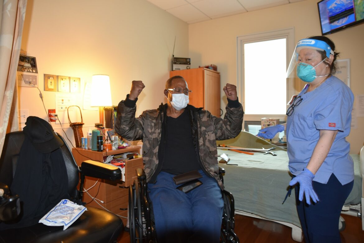Man in wheelchair raises his arms as nurse in face shield stands by. San Francisco moves to increase the number of COVID-19 vaccinations as the city struggles with the final holiday surge of cases. Photo of Laguna Honda patient preparing to be vaccinated.