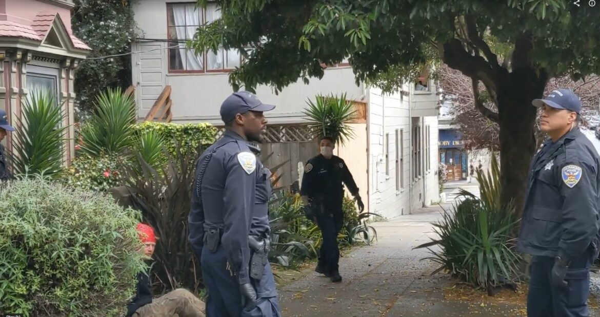 A man sits on the sidewalk with has hands restrained behind him while police officers look on.Four police officers responded to a call in March 2020 about a homeless man in the Castro.