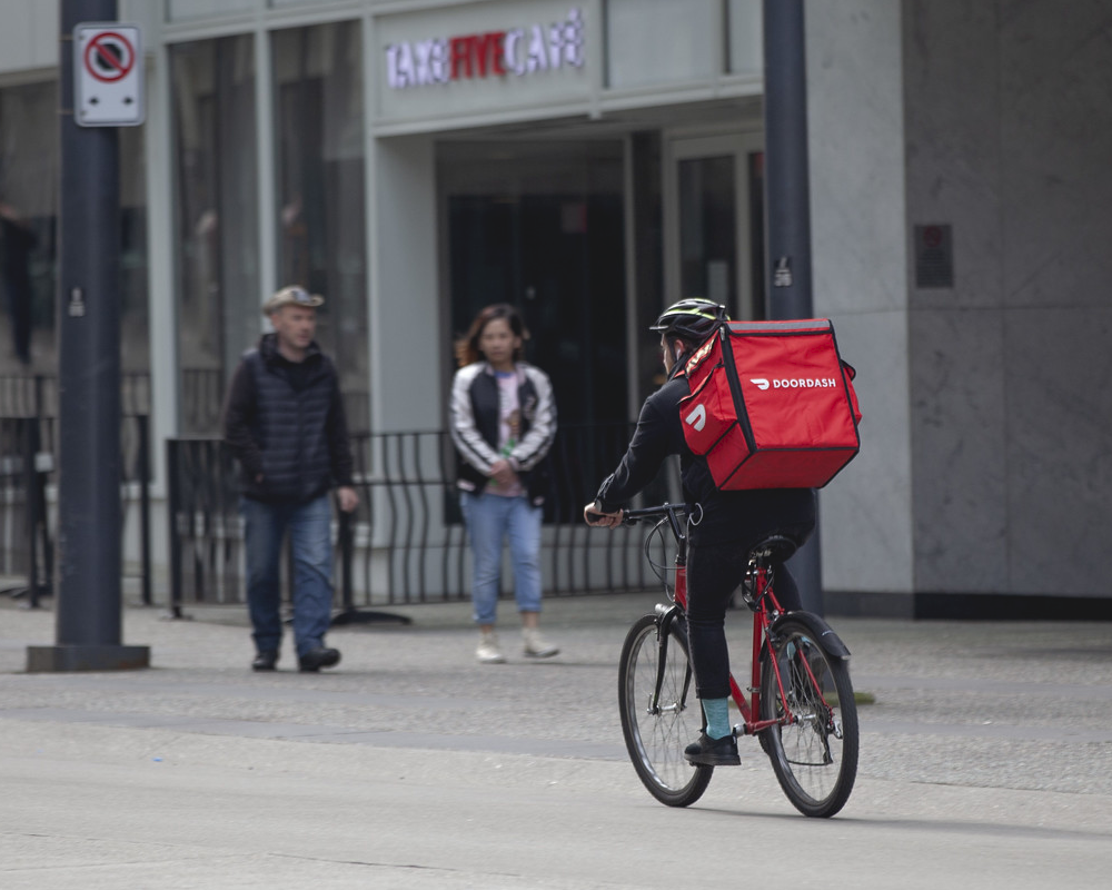 In this photo, a DoorDash delivery person rides a bicycle to make a deliver. Albertsons, Safeway's parent company, plans to cut hundreds of grocery delivery positions in California and replace them with gig workers from DoorDash.