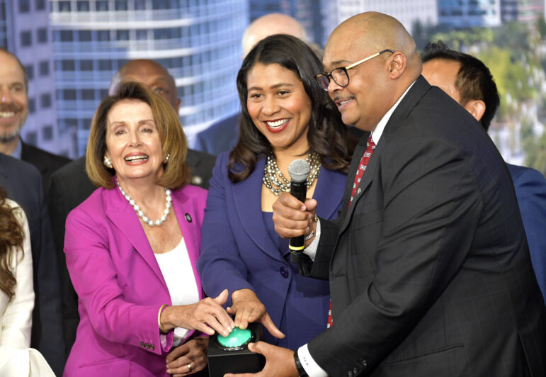 Speaker of the House Nancy Pelosi, left, and San Francisco Mayor London Breed, center, join then-Transbay Joint Powers Authority Board Chair Mohammed Nuru in turning on a bus schedule screen to celebrate the opening of the new Salesforce Transit Center.