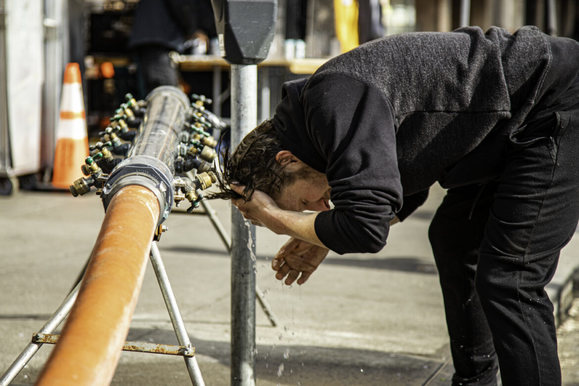 Tony Campana washes his face at a water pipe installed by San Francisco in the Tenderloin.