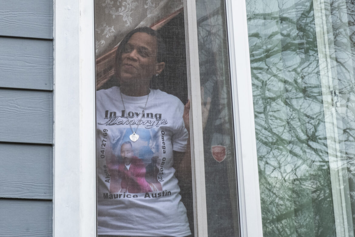 Keeshemah Johnson peers out the window of the home she once shared with her partner, Maurice Austin. Her T-shirt pays tribute to Austin.