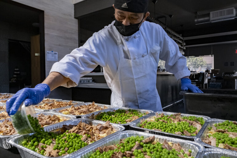 Line cook Jose Mcha prepares turkey and pasta dinners for charity distribution.