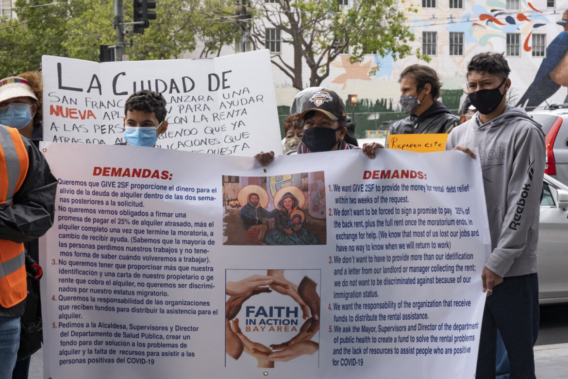 Protesters hold a sign listing demands, in English and Spanish, regarding San Francisco's rent assistance program.
