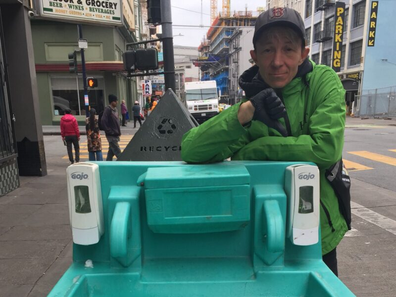 A Homeless Outreach Team worker inspects a handwashing station and finds that it needs to be refilled in the summer of 2020, at a time when coronavirus health and safety guidelines emphasized hygiene, not masks, as the best method to contain the spread of COVID-19.