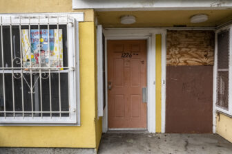 Two front doors to apartments at Plaza East, the one on the right boarded up.