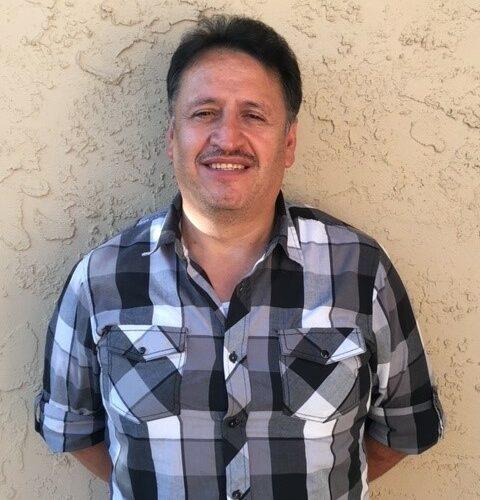Juan Hernandez stands against a wall.