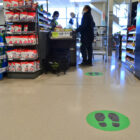 Markings on a store floor indicate where customers should stand to maintain social distance.
